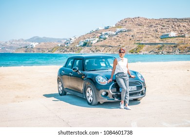 Mykonos Greece April 2018, Mini car on the beach during road trip Mykonos,woman posing by car