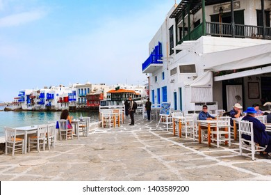 Mykonos, Greece - April 23, 2019: People, promenade with chairs and tables in typical greek tavern in Little Venice part of Mykonos town,