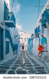 Mykonos Greece, happy Young couple in the narrow street of Mikonos with colorful blue balcony and whitewashed buildings