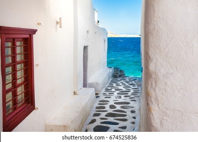 Mykonos (Greece) July 2017. A view of a traditional street in Mykonos island with a clear blue sea in the background.