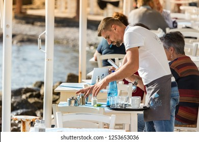 Mykonos, Greece - October 12th, 2018: A male waiter clearing a table outdoors at a greek tavern in the waterfront of Mykonos, Greece.