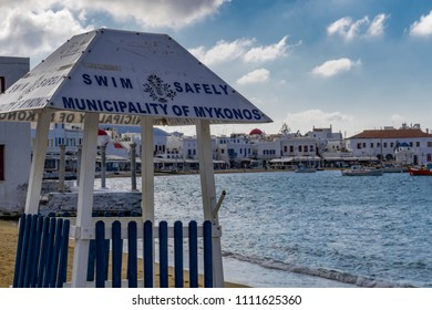 Mykonos, Greece - October 26 2017: Swim safely sign. Mykonos Municipality safety sign on lifeguard tower at public free beach with background town waterfront view and municipality house to the right.