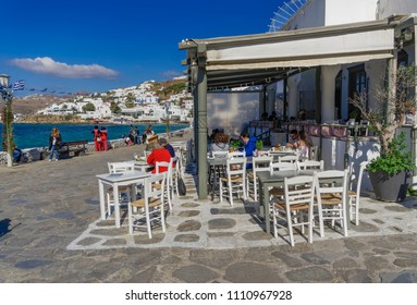 Mykonos, Greece - October 27 2017: Crowd at tavern style fast food restaurant. People eating on outdoor seating white tables by the town waterfront in central Manto Square with background town view.