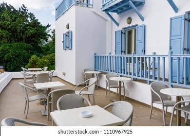 Mykonos, Greece traditional apartment house external view. Day view of hotel entrance atrium with white walls and blue balconies with dining chairs and tables next to public courtyard.