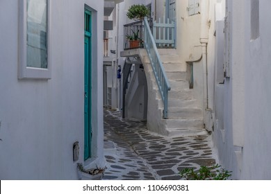 Mykonos, Greece whitewashed alleys. Traditional dotted narrow alleys with painted doors and white stairs at Mykonos Town (Chora).