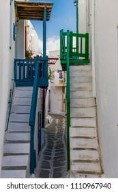 Mykonos, Greece whitewashed alleys. Traditional dotted narrow alleys with painted balconies and white stairs at Mykonos Town (Chora).