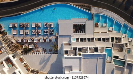 Mykonos island, Cyclades / Greece - July 14 2018: Aerial drone photo of Cavo Tagoo luxury resort famous for number of pools in new public port of Mykonos island, Cyclades, Greece