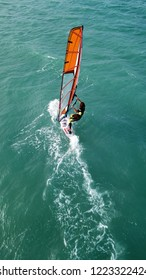 Mykonos island, Cyclades / Greece: July 20 2018: Aerial drone photo of wind surfer cruising in high speed in popular wavy beach of Super Paradise
