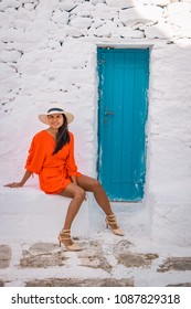 Mykonos island  Greece, colorful Mikonos town,young woman with red dress on a white wall and blue door