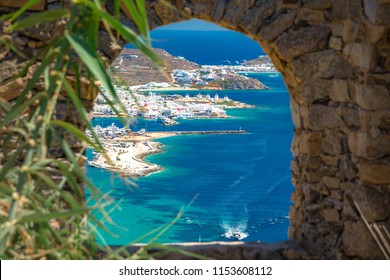 Mykonos port with boats and windmills through a frame of stone window, Cyclades islands, Greece