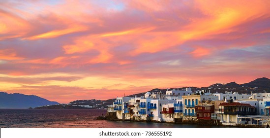 Mykonos sunset over the Little Venice buildings next to the sea with mountains behind them in the background.
