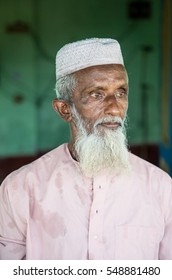 MYMENSINGH BANGLADESH - JANUARY 3, 2017: An older islamic muslim man with white beard and wrinkled old face and green background portrait