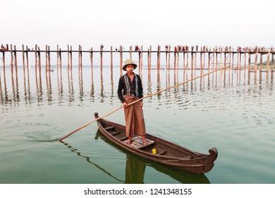 Mynamar / Amarapura - 07/03/2018: Tourist boat on Taung Thama Lake and U Bein bridge at Amarapura, Mandalay Province, Myanmar, Asia.
