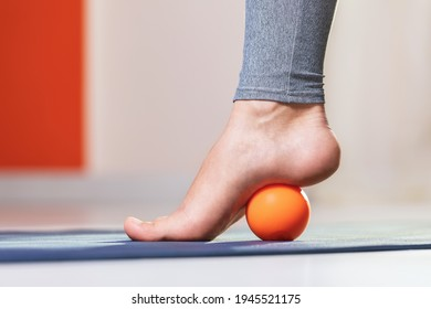 Myofascial relaxation of the muscles of the foot with a massage ball on a mat at home, close-up. Concept on the topic of preventing foot fatigue after wearing high-heeled shoes.