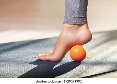 Myofascial release of hyper-movable muscles of the foot with a massage ball on a gymnastic mat at home. Prevention of leg fatigue after wearing high heel shoes.