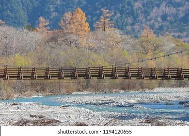 MYOJIN bridge among natural river and autumn forest at Kamikochi Nagano JAPAN.
