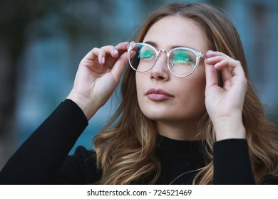 Myopia, close-up portrait of young woman student in eyeglasses for good vision looking up, blue building background