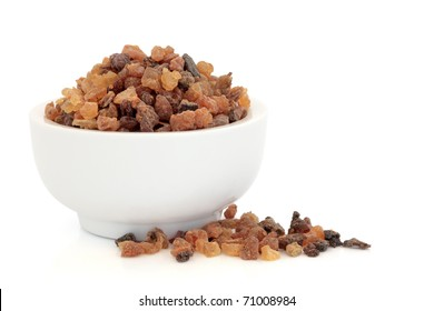 Myrrh oleo gum resin in a porcelain mortar and scattered, over white background.