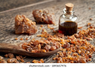 Myrrh resin on a spoon, with essential oil in the background