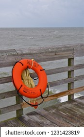 Myrtle Beach, SC / USA - August 26 2011: A orange life preserver hangs on the fishing pier at Myrtle Beach State Park.  MB State Park offers a quiet escape from the otherwise busy beach.