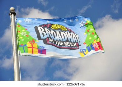 Myrtle Beach, SC / USA - December 18 2012: A Christmas themed flag  blows in the wind at Broadway at the Beach. A popular shopping center and entertainment complex located at the beach.