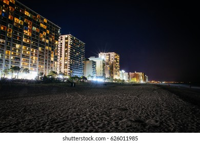MYRTLE BEACH, SOUTH CAROLINA - 13 APRIL 2017: Beachgoers stroll along the water's edge after dark.