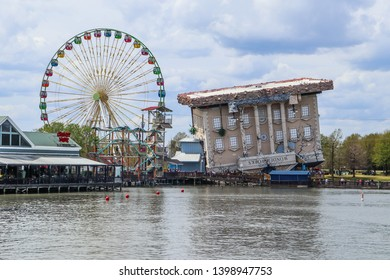 MYRTLE BEACH, SOUTH CAROLINA/USA - MARCH 29, 2019: The upside-down Wonderworks educational/entertainment venue on the harbor of Broadway at the Beach, surrounded by a ferris wheel and restaurants.