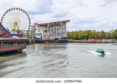 MYRTLE BEACH, SOUTH CAROLINA/USA - MARCH 29, 2019: A jet boat speeds by the upside-down Wonderworks educational/entertainment venue, a ferris wheel and shops at Broadway at the Beach.