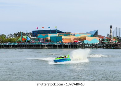 MYRTLE BEACH, SOUTH CAROLINA/USA - MARCH 29, 2019: A jet boat ride carries passengers for a thrill ride at Broadway at the Beach entertainment complex, with the Ripley's Aquarium in the background.