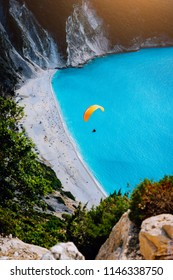 Myrtos Beach, Kefalonia Island, Greece. Figure of a parachutist skydiver with orange parachute against a blue lagoon bay beach