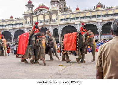 MYSORE, INDIA - OCTOBER 11: People watching parade / procession on Dussehra  festival, men riding on decorated elephant with umbrella at Mysore maharajas Palace on October 11, 2016 Karnataka, India.