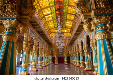 Mysore, Karnataka, India - November 25th 2018 : Beautiful decoated interior ceiling and pillars of the Ambavilasa Hall, inside the royal Mysore Palace. Gold used on gilded columns and glass ceiling.