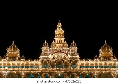 Mysore palace lit up at night with a dark black sky above.