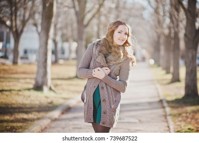 Mysterious adorable young brunette lady portrait with cute face and seducing lips professionally posing sit for camera wearing cosy warm designer clothes with fur in autumn spring central park.