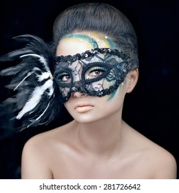 Mysterious beautiful girl in a black mask with feathers with green creative makeup in the studio on a dark background isolated