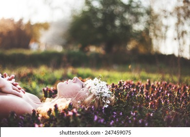 mysterious beautiful girl with flowers in her hair. Queen blooming gardens. Fields of flowers