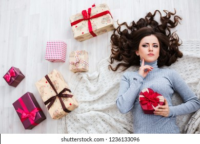 Mysterious Beautiful woman lying on the floor with gift boxes. Choose a gift for the holiday.
