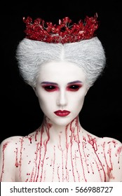 Mysterious beauty portrait of snow queen covered with blood. Bright luxury makeup. Black demon eyes