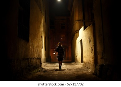 Mysterious blonde woman in elegant retro coat with old oil lantern walking in old French street in Paris, noire atmosphere, investigating crime, detective concept