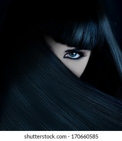 mysterious brunette with hair covered face and aquamarine eyes