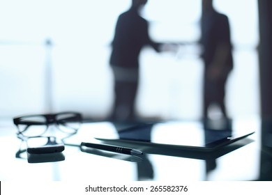 Mysterious business, business meeting. Blurred figure of a man in an office building, a desk workstation