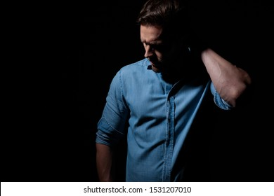 mysterious casual man wearing blue shirt standing in the shadows and scratching his head pensive against black studio background