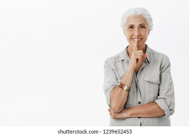 Mysterious creative and carefree elderly woman in casual outfit making shh or shush gesture with index finger over mouth smiling hiding secret wanting make surprise for son who getting married