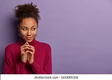 Mysterious curly haired woman keeps hands together with intention to do something, looks with intrigued expression aside, wears casual jumper, has interesting plan, isolated on purple background