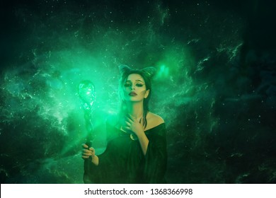 mysterious dark elf got terrible curse, charming girl with horns on head and glowing sparkling magic stick in hands, damned lady in green electric fire puts her hand on neck, creative art photo