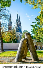 The mysterious Devil's Column at Vysehrad in Prague with St. Peter's and St. Paul's basilica in the background