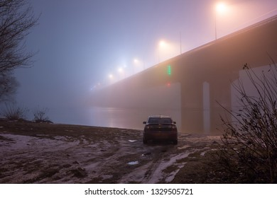 A mysterious evening fog above the river in big city. Bridge in the mist, cold weather scenery. Soft, blurry, misty look. Colorful, mystic industrial cityscape. A car on the river bank.