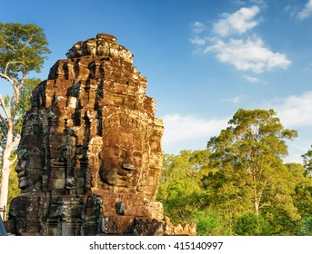 Mysterious face-tower of ancient Bayon temple in Angkor Thom in evening sun. Siem Reap, Cambodia. Woods and blue sky in background. Angkor Thom is a popular tourist attraction.