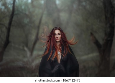 Mysterious fantasy gothic woman dark witch obsessed by evil. Red-haired Girl demon in black dress cape hood. Red hair flutters in wind. Dark dense deep forest background, trees. Scleral lenses on eyes