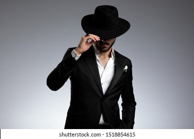 mysterious fashion model wearing tuxedo, pulling hat down, on grey background in studio
